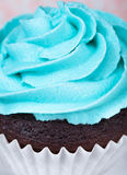Blue icing. Close up of a chocolate cup cake with blue icing stock photography