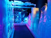 Blue illuminated ice corridor magic underwater world. A corridor made of ice looking like an underwater world with sculptures of swimming penguins and fishes stock photography