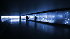 Blue illuminated underpass / subway - people walking by. Silhouettes of unrecognisable people walking by in front of a blue illuminated glass wall. Pedestrian stock video