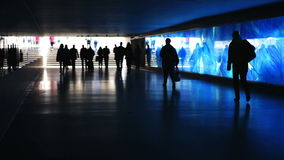 Blue illuminated underpass / subway - people walking by. Silhouettes of unrecognisable people walking by in front of a blue illuminated glass wall. Pedestrian stock video footage