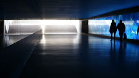 Blue illuminated underpass / subway - people walking by. Silhouettes of unrecognisable people walking by in front of a blue illuminated glass wall. Pedestrian stock footage