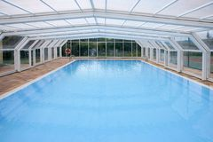Blue indoor beautiful pool with glasshouse Royalty Free Stock Image