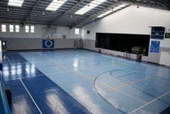 Blue Indoor Gymnasium. Indoor modern gymnasium - basketball court/stage, high school, middle school, elementary school stock photo