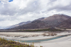 The blue Indus river in front of the snow mountain. Blue Indus river in Leh Ladakh is flowing in front of the snow mountain Royalty Free Stock Images