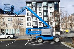 Blue Industrial Cherry Picker Crane. At parked in parking lot stock images