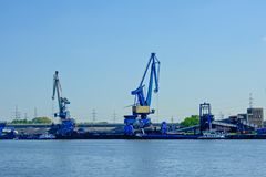 Blue industrial cranes in the harbor of Ghent, Belgium. Big blue industrial loading cranes on a quay along a canal in the harbor of Ghent, Belgium Stock Photos