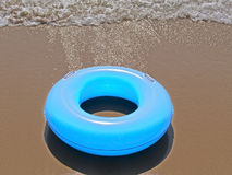 A blue inflatable donut on the seashore. An inflatable donut on the seashore Royalty Free Stock Photos