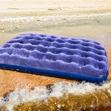 Blue inflatable mattress swimming in the pond. An inflatable mattress on the beach stock images