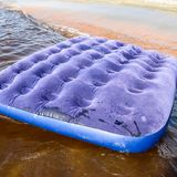 Blue inflatable mattress swimming in the pond. An inflatable mattress on the beach royalty free stock image