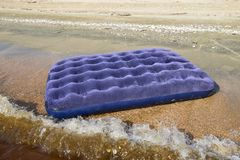 Blue inflatable mattress swimming in the pond. An inflatable mattress on the beach royalty free stock photos