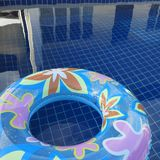 Blue inflatable round tube with flower design on the swimming pool. In resort Stock Photo
