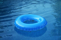 Blue Inflatable Wheel. A blue inflatable wheel or tire is floating in the pool Stock Image