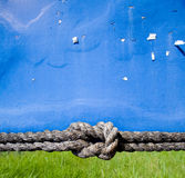 Blue information wall. With rope with a knot on the bottom Stock Photo