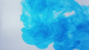 Blue ink dropped into water in slow motion stock video