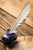 Blue ink with feather on old vintage letter. On old wooden table Royalty Free Stock Photo