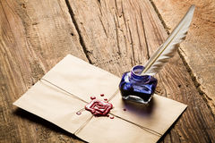 Blue ink inkwell and envelope with red sealant. On old wooden table stock image