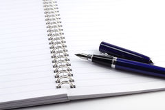 Blue ink pen on notebook Royalty Free Stock Photos