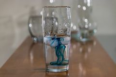 Blue ink in water glass on table top. Blue ink swirling in water with other empty glasses behind on table royalty free stock images