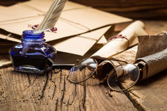 Blue inkwell and glasses surrounded by ancient messages and envelopes. On old wooden table royalty free stock photos