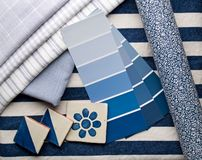 Blue interior decoration plan. Blue paint color and fabric swatches with handcrafted ceramic tiles and a wallpaper roll Stock Photography