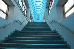 Blue interior with staircase. Interior of a modern building with ascending staircase and blue transparent roof Royalty Free Stock Photos