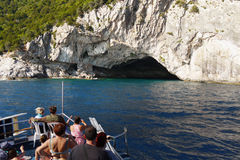 Blue Ionian Sea and Cave,  Island Boat Trip. Blue Ionian Sea and coast cave. Tourists on boat trip around island. Greece Stock Image
