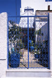 Blue Iron Fence in Greece. Blue decorative iron fence on a Greek island with a blue pot and a blue sky Stock Photo