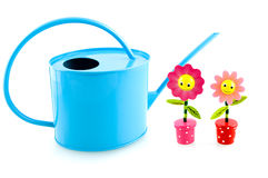 Blue iron watering can with wooden flowers. Isolated on white background Stock Images