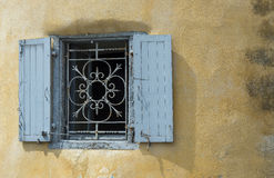 Blue iron window on a worn stucco wall. Royalty Free Stock Photography