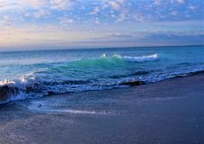Blue Island waves with the sunrise reflection bring a colorful vista to the Boca Raton Beach. The beach at sunrise in Boca Raton is second to none in beauty with Stock Photos