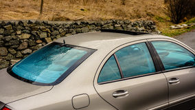 Blue isolated/tinted windows and open sun roof - german sedan car in gold metallic. Cluj-Napoca, Romania - August 08, 2017: Isolated blue tinted windows Stock Images