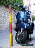 Blue Italian Scooter. A shiny blue italian scooter parked on a narrow street in Italy Royalty Free Stock Image