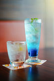 Blue itallian soda iced and drinking water in a glass  on wood table, selective focus on green leaf, filtered image Royalty Free Stock Photography