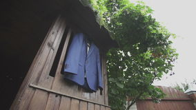 Blue jacket hanging on the wood background. Hd stock video footage