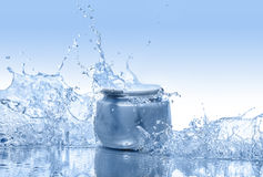 The blue jar of moisturizing cream stays in the  water splashes on the gradient blue background Stock Photography