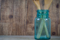Blue jar in rustic setting. Old blue jar with wooden spoons against an old wood background Royalty Free Stock Images