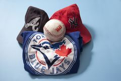 Blue Jays shirt, Braves and Yankees caps against a blue background. Halifax, Nova Scotia, Canada- June 16, 2019: Major League Baseball gear, shirt and a ballcap royalty free stock photo