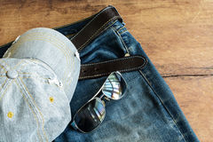 Blue jean and cap on old wood Stock Photos