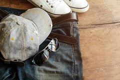 Blue jean, cap and shoes on old wood background Stock Image