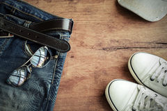 Blue jean, cap and shoes on old wood background Stock Images