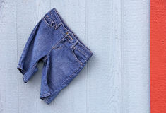 Blue Jean Capri Shorts on blue grey wall red border Stock Photography