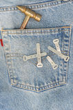 Blue jean with hammer in the pocket. Blue jean on black with hammer in the pocket Royalty Free Stock Image