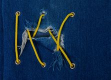 Blue jean with hole and crisscross lacing. Blue jean with hole and crisscross yellow lacing stock photography