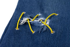 Blue jean with hole and crisscross yellow lacing Royalty Free Stock Photography