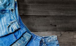 Blue jean and jean lack texture on the wooden floor. Pattern of blue jeans are overlapping on the table and free space Stock Photos
