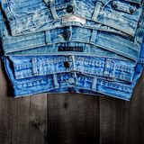 Blue jean and jean lack texture on the wooden floor. Pattern of blue jeans are overlapping on the table and free space Stock Photo