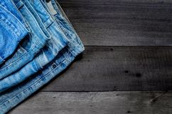 Blue jean and jean lack texture on the wooden floor. Pattern of blue jeans are overlapping on the table Royalty Free Stock Photo