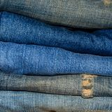Blue jean and jean lack texture on the wooden floor. Pattern of blue jeans are overlapping on the table Stock Image