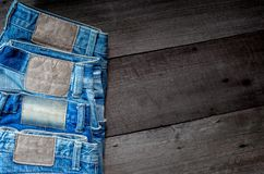 Blue jean and jean lack texture on the wooden floor. Pattern of blue jeans are overlapping on the table and free space Royalty Free Stock Image