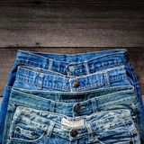 Blue jean and jean lack texture on the wooden floor. Pattern of blue jeans are overlapping on the table and free space Stock Photography